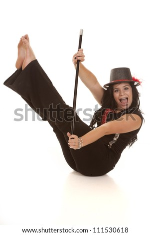 A teen girl sitting on the floor holding her cane with a big smile on her face. - stock photo