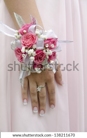 A teen girl with a wrist corsage on prom night.