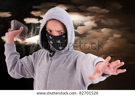 A teen with a rock, in a act of juvenile delinquency, with clouds of smoke background - stock photo
