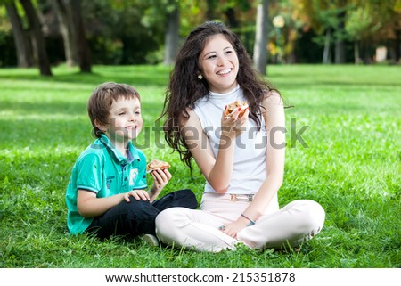 A teenage asian caucasian girl with long curly brown hair with a boy laughing and having good time sitting on the green grass in the park eating a muffin - stock photo