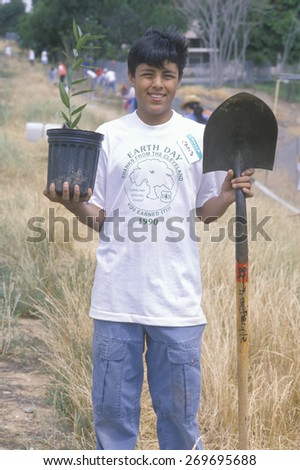A teenage boy holding a plant and a shovel during Earth Day participation - stock photo