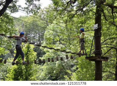 A teenage boy is climbing on the rope ladder. A preteen girl is standing on the platform high up. They are at the rope parkour. - stock photo