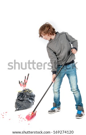 a teenage boy with a broom, cleaning the mess on new years day