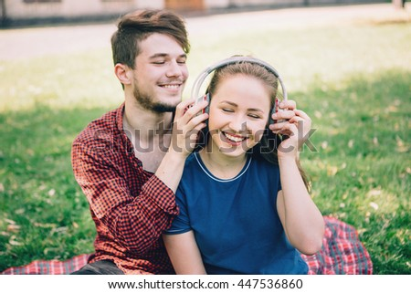 A teenage couple listening to music.