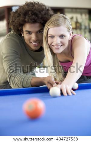A teenage couple playing pool - stock photo