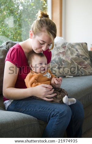 A teenage girl holding her nephew indoors.