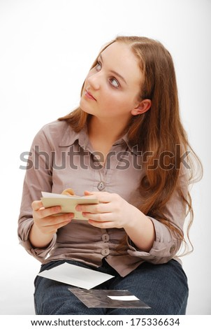 A teenage girl holds a card in her hands. She is sitting and looking upwards. She is wearing a blouse and jeans. - stock photo