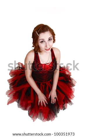 A teenage girl in an red and black ballet outfit kneeling on the floor, looking up into the camera, for white background.