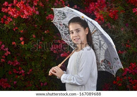 A teenage girl in white with colorful bougainvillea flowers and a white umbrella - stock photo
