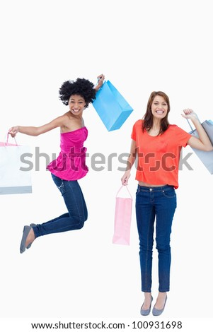 A teenage girl leaping while holding her shopping bags while her friend is smiling - stock photo