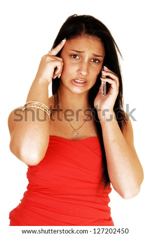 A teenage girl on the cell phone getting a very bad news and is worried, in a strapless red dress and long black hair for white background. - stock photo