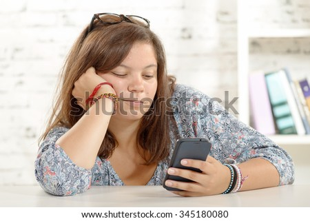 a teenage girl playing with her phone - stock photo