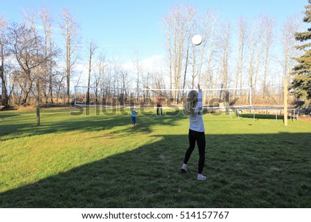 A teenage girl practicing serving volleyball over net in backyard with her father