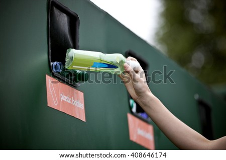 A teenage girl recycling a plastic bottle - stock photo