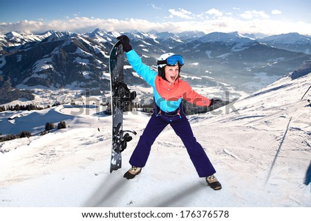a teenage girl snowboarding in the Alps. - stock photo