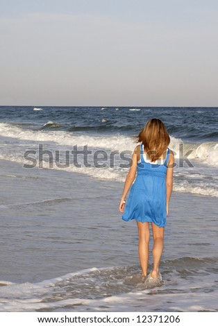 A teenage girl walking on the beach.