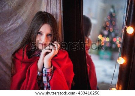 a teenage girl was hiding a red blanket, sitting near the mirror which reflects the Christmas tree - stock photo