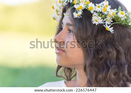 A teenage girl with a wreath of daisies on the nature