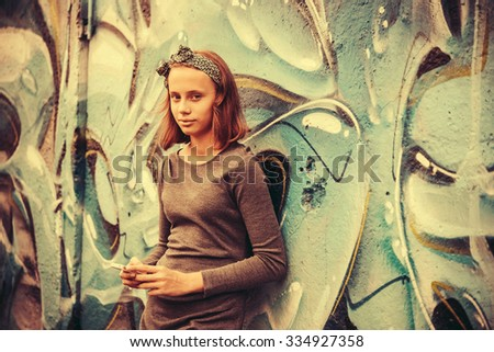 A teenage girl with smartphone leaning against the wall with graffiti. Toned image