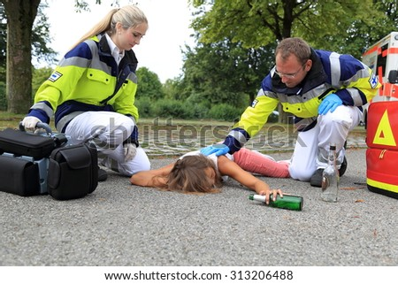A Teenager drunken on floor with paramedic - stock photo