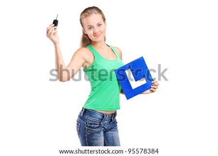 A teenager holding a L plate and car key isolated on white background - stock photo