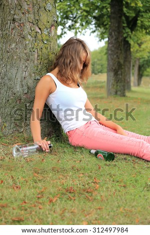 A Teenager leaning drunken on a tree with bottle - stock photo