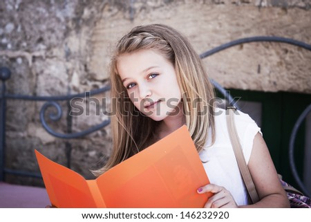 A teenager reading from a file, looking at camera, positive feeling, candid shot