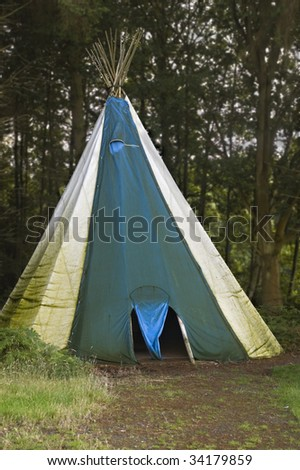 A teepee, similar to those used by native Americans, at a campsite in the woods