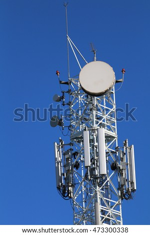 A telecommunications antenna or tower against a blue sky.