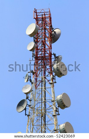 A telecommunications tower with a clear blue sky