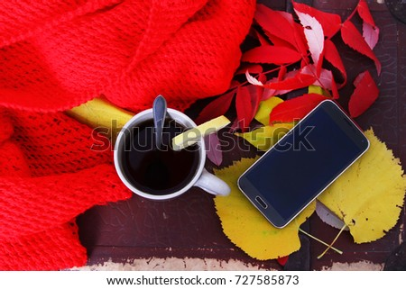 A telephone and a glass of tea with an autumn leaf arrangement.