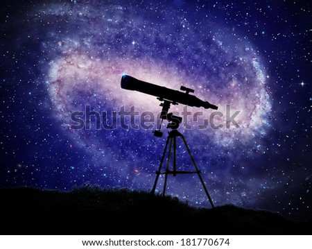 A telescope with a large spiral galaxy in the background - stock photo