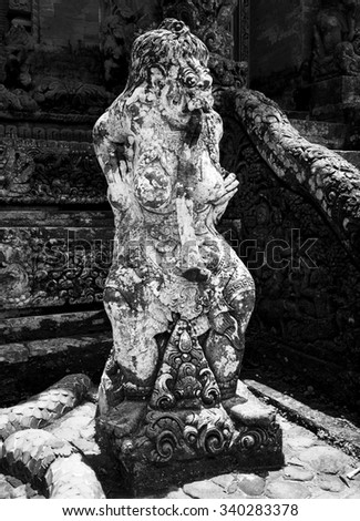 A temple statue representing a female goddess stands near the staircase to an interior sanctuary in the Monkey Shrine temple in Ubud on Bali, Indonesia. - stock photo