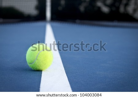 A tennis ball on the line at dusk. - stock photo