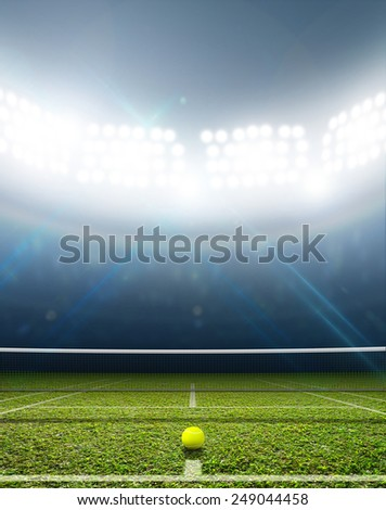 A tennis court in an arena with a marked green lawn surface at night under illuminated floodlights - stock photo