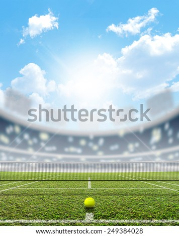 A tennis court in an arena with a marked green lawn surface in the daytime under a blue sky - stock photo