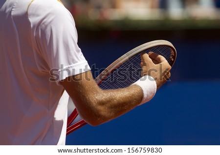 A tennis player checks racquet for serve a tennis ball during a match - stock photo