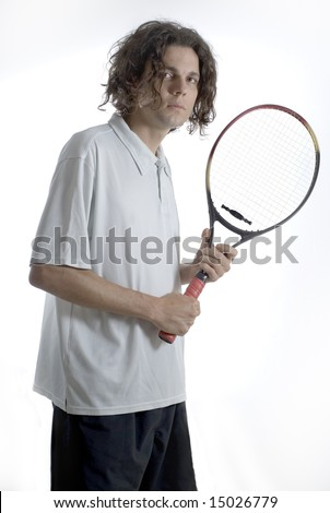 A tennis player holding a racket and looking timidly at the camera. Vertically framed shot. - stock photo