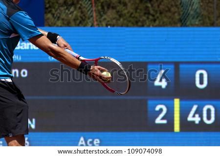 A tennis player prepares to serve a tennis ball during a match - stock photo
