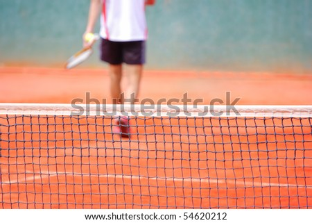 A tennis player walking out of a tennis court - stock photo
