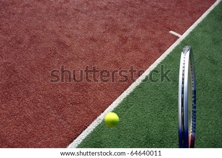 A tennis racket and tennis ball, sports photo