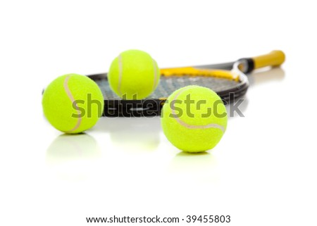 A tennis racket with three tennis balls on a white background - stock photo