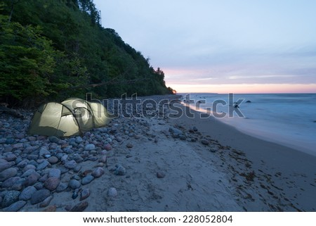 A tent at the coast at sunset - stock photo