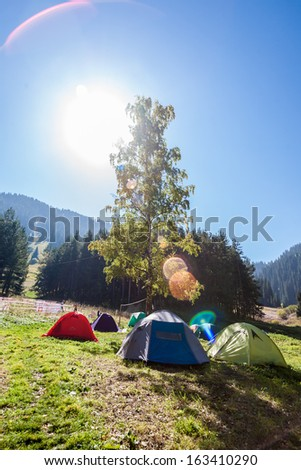 A tent camp in the mountains near the forest - stock photo
