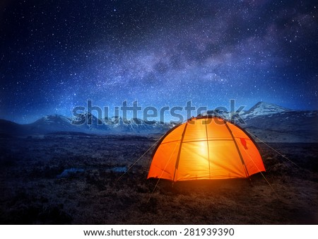 A tent glows under a night sky full of stars.  - stock photo