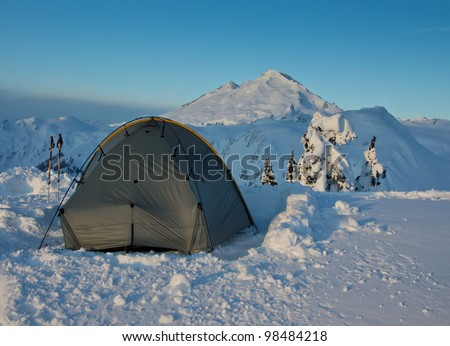 a tent is pitched in snow with Mt. Baker in Washington State in background - stock photo