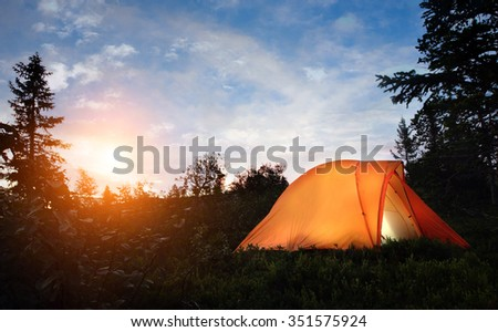 A tent lit up at dusk  - stock photo