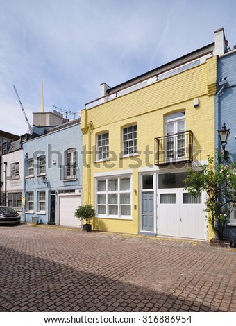 A terrace of mews houses converted from 18th century stable carriage buildings in Kensington, London, UK. - stock photo