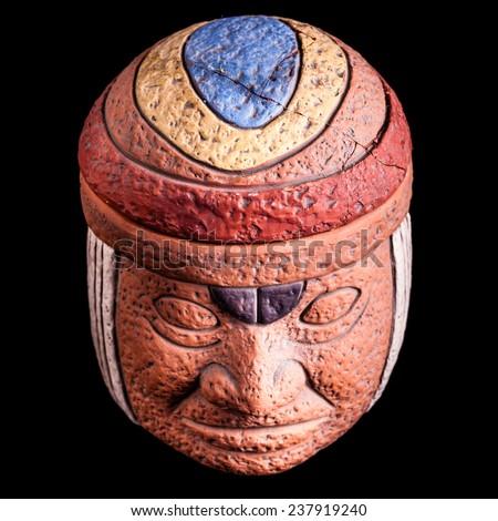 a terracotta olmec face idol souvenir isolated over a black background - stock photo