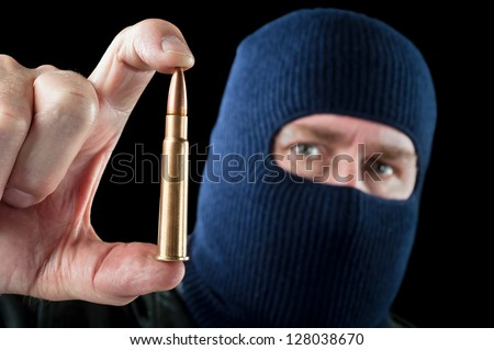 A terrorist wearing a ski mask as a disguise holds out a large automatic rifle bullet. - stock photo